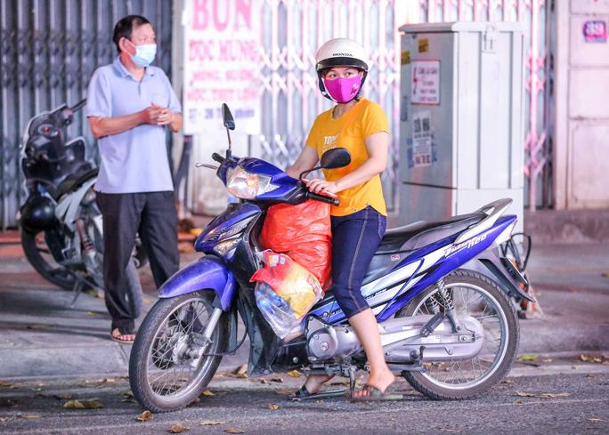 Người dân mặc áo mưa tiếp tế lương thực vào trung tâm thương mại bị phong toả - Ảnh 11.