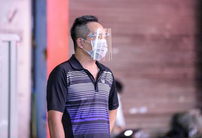 Người dân mặc áo mưa tiếp tế lương thực vào trung tâm thương mại bị phong toả - Ảnh 14.