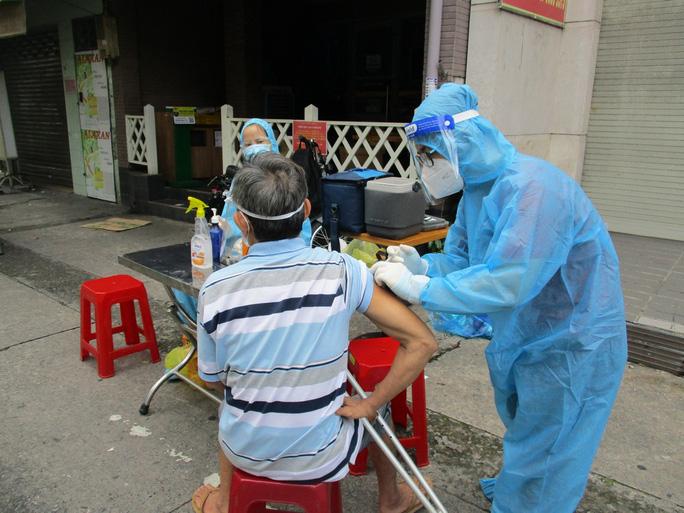 Cận cảnh đội tiêm lưu động đến tận tổ dân phố tiêm vắc-xin cho người dân - Ảnh 3.