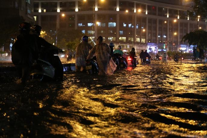 CSGT dầm mưa giúp dân qua đoạn ngập ở Sài Gòn - Ảnh 2.