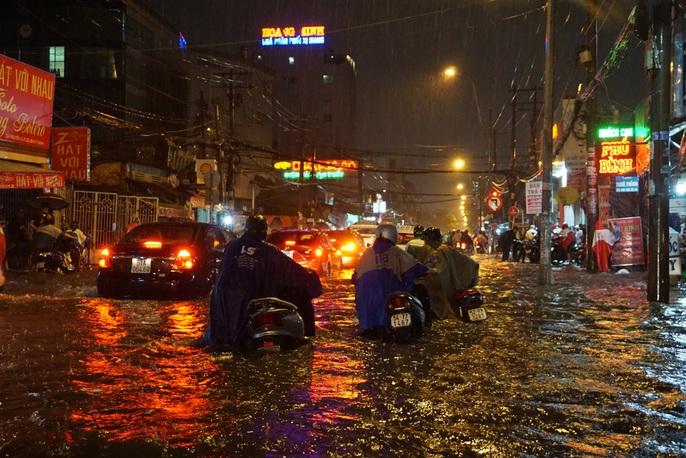 Nước chảy như lũ ở TP HCM sau cơn mưa lớn - Ảnh 4.