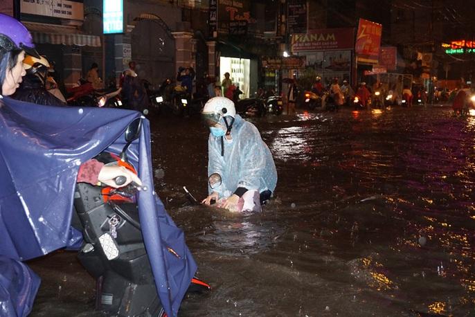 Nước chảy như lũ ở TP HCM sau cơn mưa lớn - Ảnh 5.