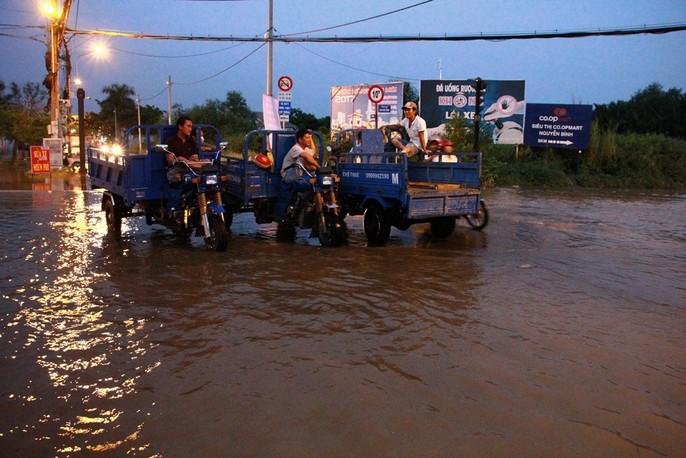 Dịch vụ ba gác giải cứu xe máy đắt khách trong triều cường - Ảnh 8.
