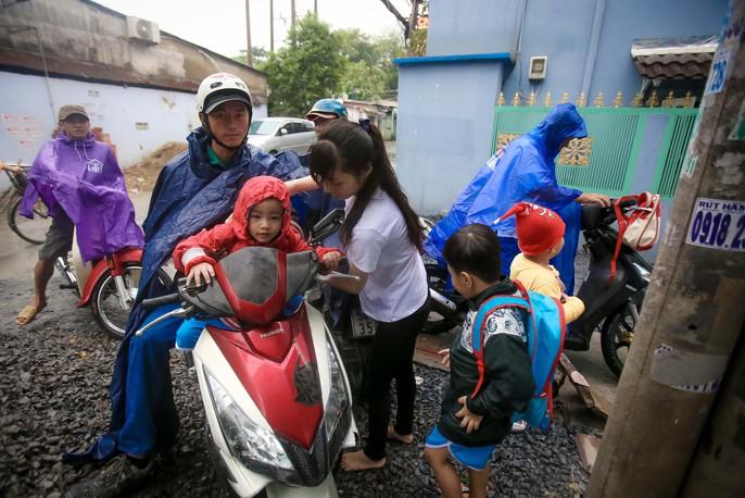 TP HCM: Phụ huynh đội mưa đón con tránh bão số 16 (Tembin) - Ảnh 3.