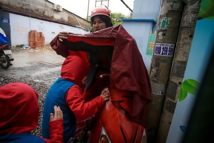 TP HCM: Phụ huynh đội mưa đón con tránh bão số 16 (Tembin) - Ảnh 6.