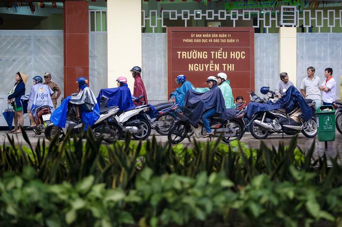 TP HCM: Phụ huynh đội mưa đón con tránh bão số 16 (Tembin) - Ảnh 9.