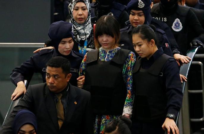 Đoàn Thị Hương (áo hoa) mặc áo chống đạn. Ảnh: Reuters