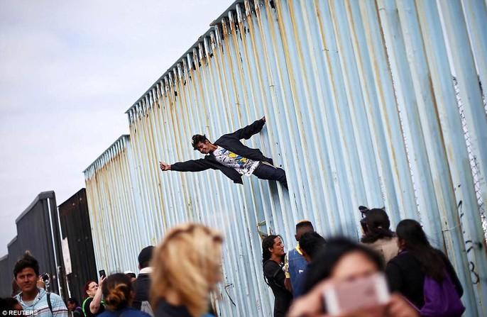 Người di cư trèo lên hàng rào biên giới Mỹ - Mexico - Ảnh 2.