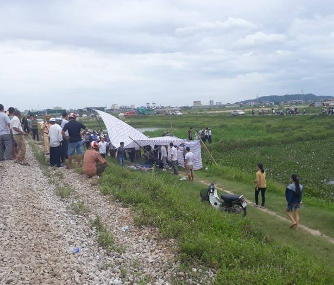 Thi thể nạn nhân được đưa ra khỏi ô tô và để cạnh đường sắt.