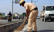 CSGT phụ công nhân quét đá dăm trên đường Phạm Văn Đồng