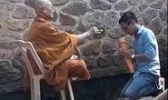 Người mặc đồ nhà sư đọc thần chú, vẩy nước thánh tại chùa Hương Tích