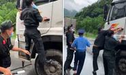 Xe tải vượt chốt kiểm soát Covid-19 trong khi một cảnh sát đang đu cửa