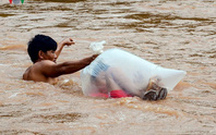 Học sinh chui túi nilon băng suối đến trường ngày khai giảng