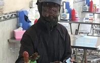 Người đàn ông bôi đen mặt, phùng má, tay cầm đầu gà đi lang thang xin tiền