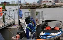 Nhiều người dùng dây cố định một thi thể trên sông Sài Gòn