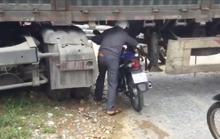 Xe chở cột điện chắn ngang quốc lộ, dân chui gầm xe qua đường