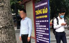 Người đàn ông không đeo khẩu trang tạo dáng chụp ảnh cạnh biển thông báo chống dịch Covid-19