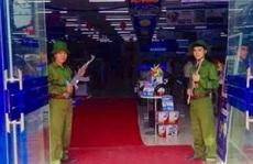 Đôi nam nữ bồng súng chào khách trước cửa siêu thị