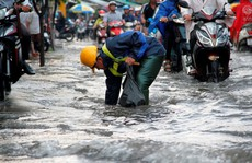 Người dân TP HCM 'bì bõm' sau cơn mưa lớn
