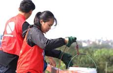 Sinh viên lên cầu Long Biên hỗ trợ người dân thả cá không thả rác