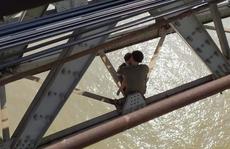 Thanh niên buồn chuyện gia đình ôm con nhỏ ngồi vắt vẻo trên thanh giằng cầu Long Biên