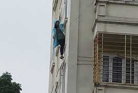 Cô gái trẻ bất ngờ đu mình ra ngoài cửa sổ chung cư rồi nhờ gọi cảnh sát giải cứu