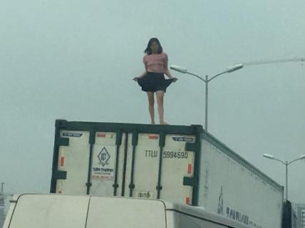 """Người phụ nữ mặc váy quậy """"tưng bừng"""" trên nóc thùng xe container"""