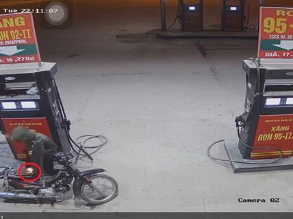 Nam thanh niên dùng bật lửa kiểm tra xăng vừa đổ vào xe máy tại cây xăng